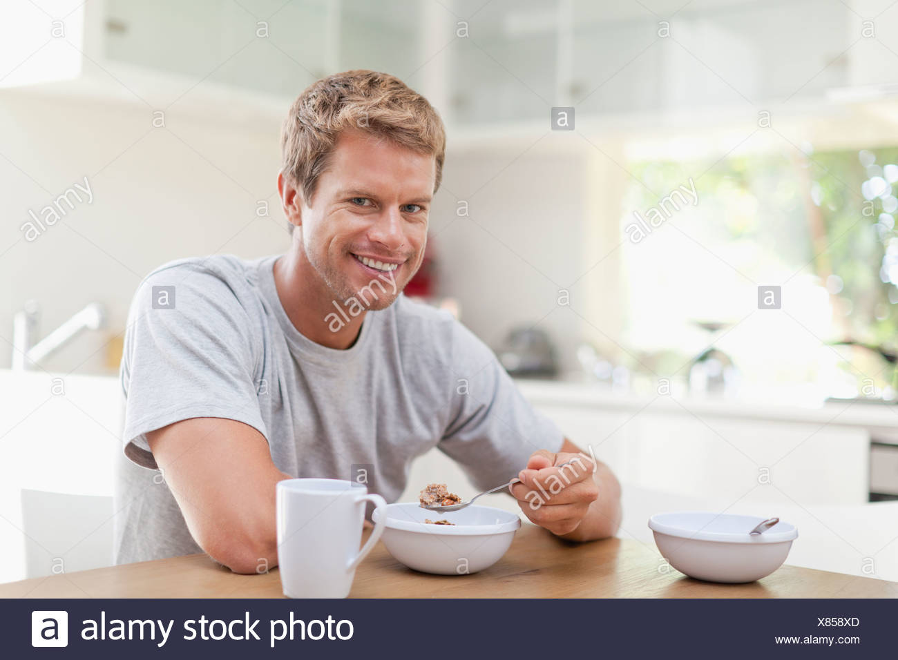 Man eating breakfast in kitchen Banque D'Images