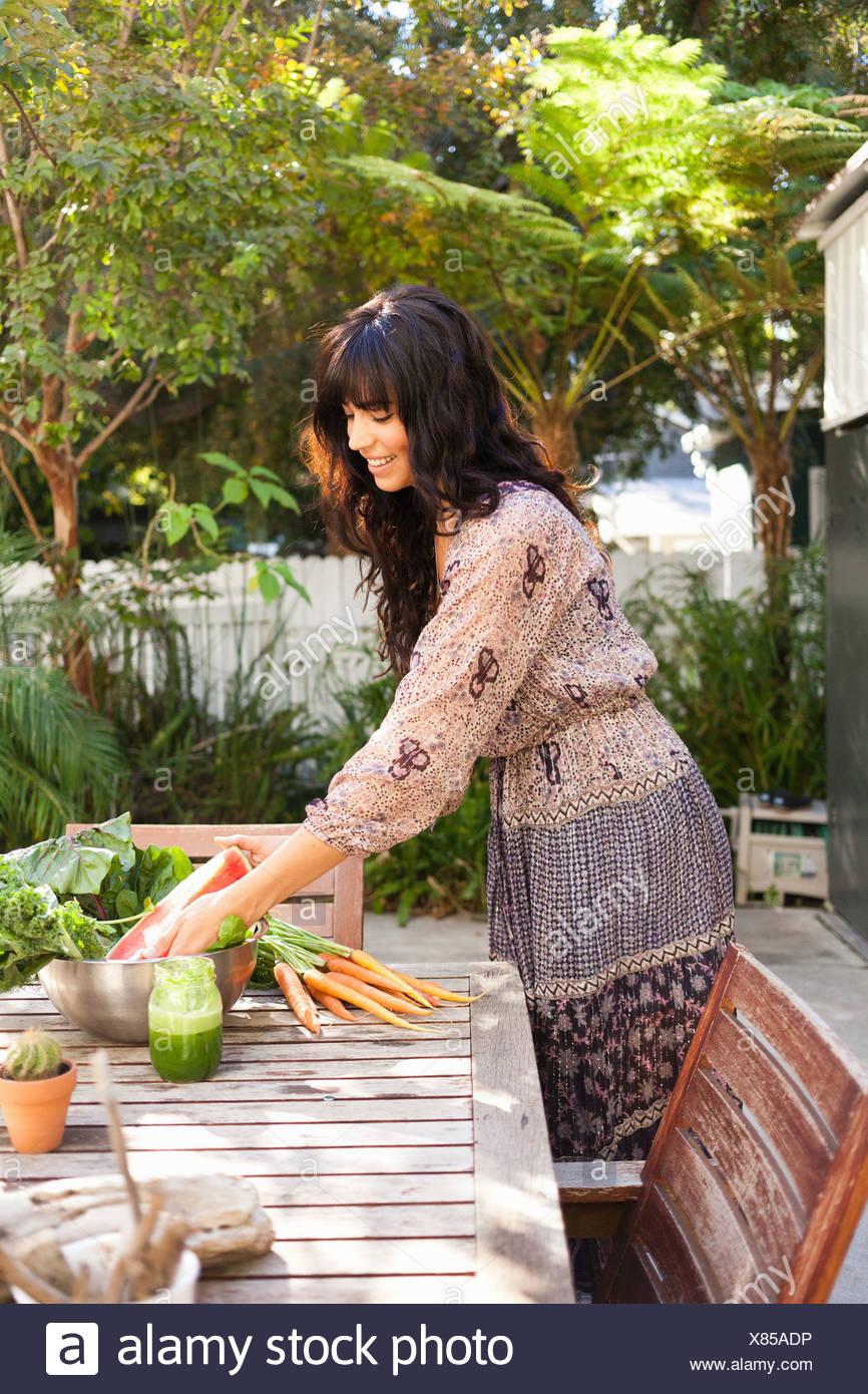 Jeune femme avec des légumes sur la table Photo Stock