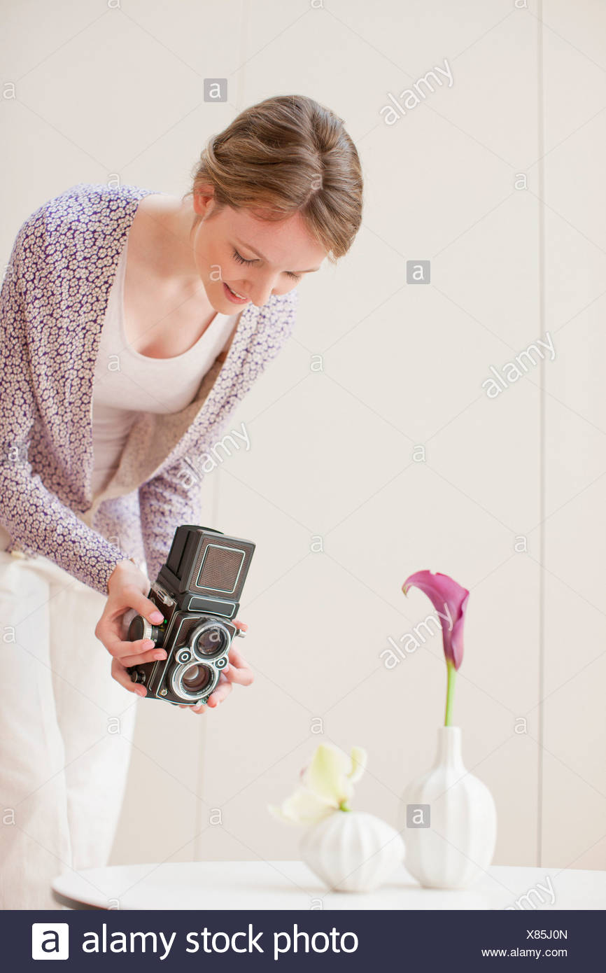 Photographier des fleurs dans des vases femme avec caméra rétro Photo Stock