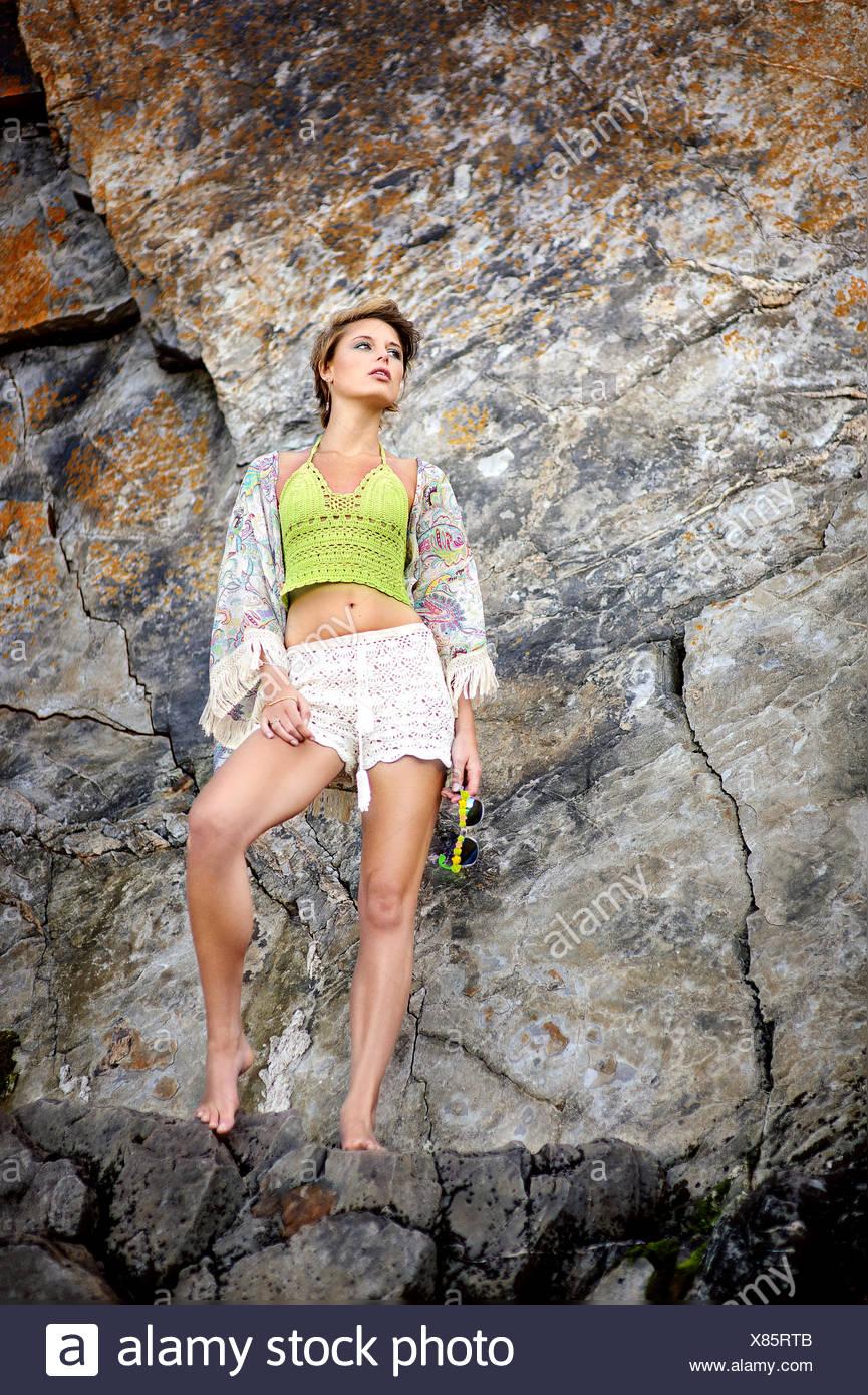Jeune femme debout à côté d'une falaise à la plage Photo Stock