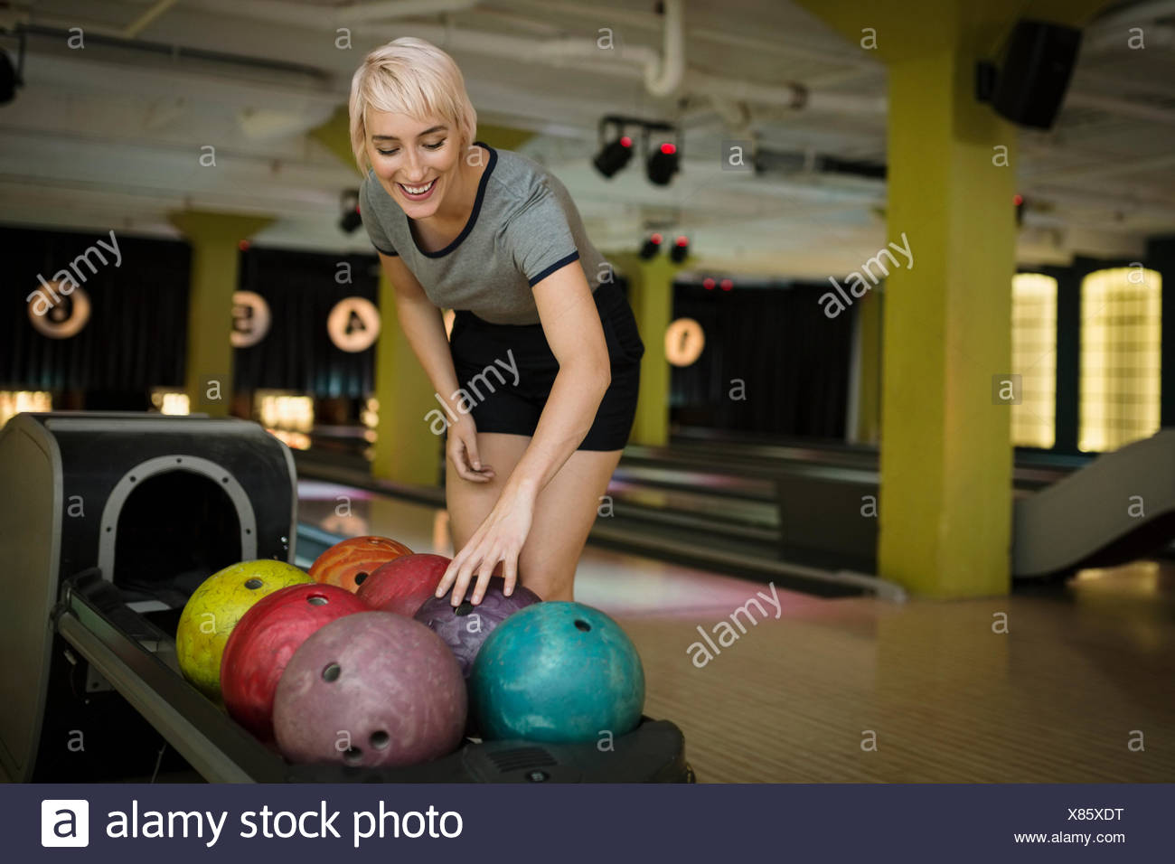 Young woman choosing bowling ball du rack Photo Stock