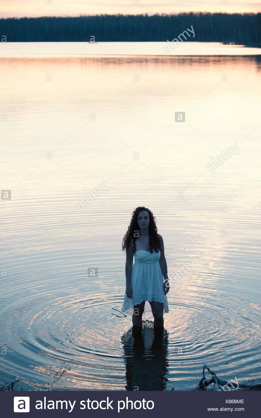 Une femme en robe blanche en eau peu profonde au crépuscule Photo Stock