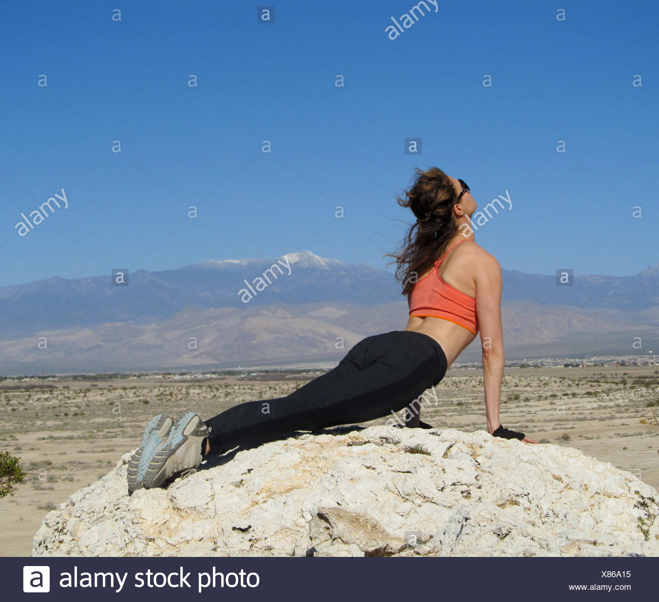 Femme faisant un cobra yoga pose sur un rocher dans le désert du Nevada, USA, Amérique, Photo Stock