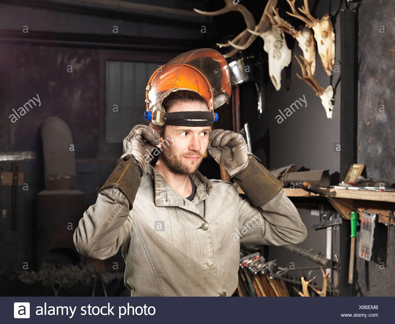 Blacksmith en mettant sur une visière en atelier Photo Stock