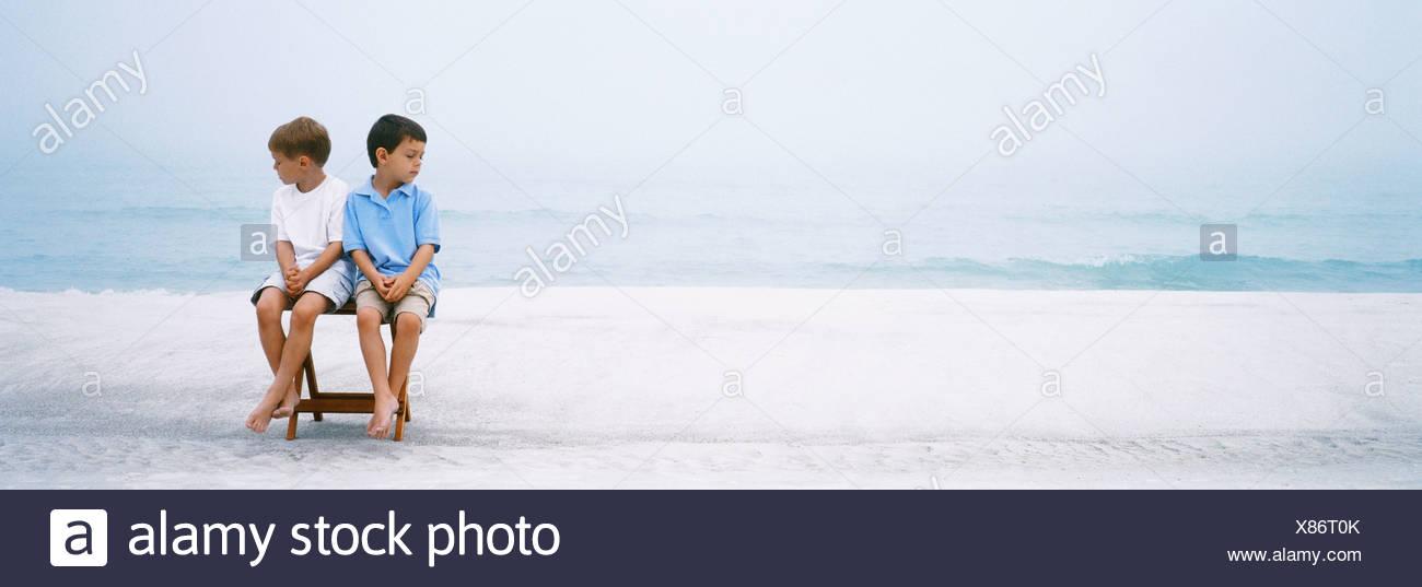 Deux garçons assis côte à côte sur chaise pliante à ignorer une autre plage Photo Stock