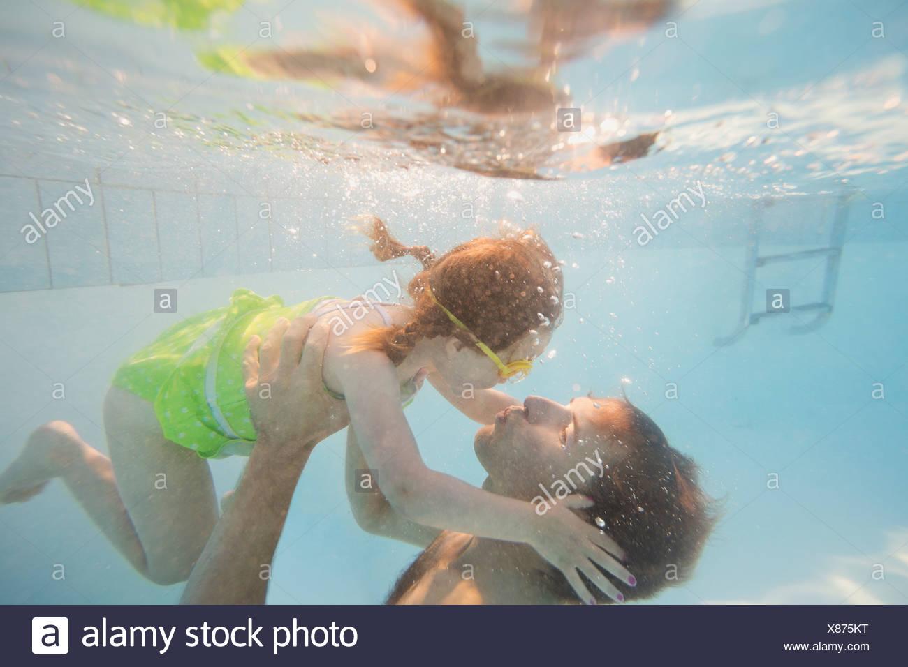 Père et fille sous l'eau à la piscine Photo Stock
