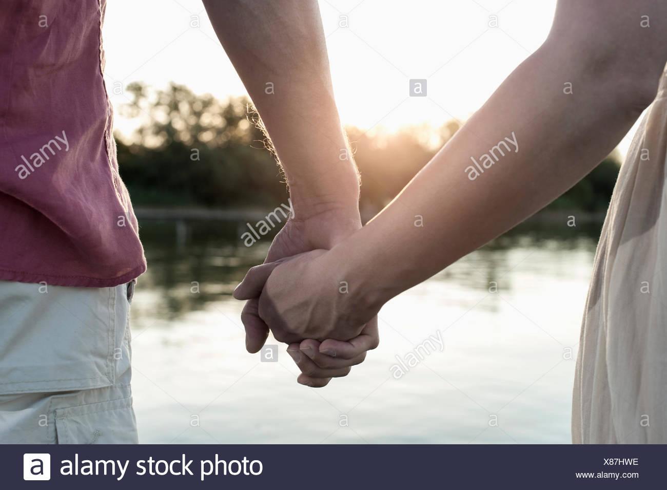 Up d'un couple amoureux se tenant la main pendant le coucher du soleil, Bavière, Allemagne Photo Stock