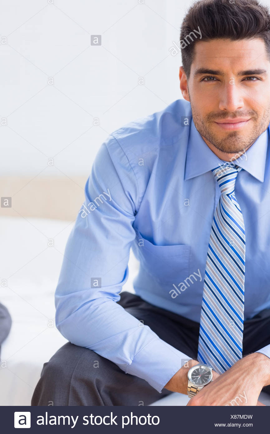Businessman sitting on bed smiling at camera Photo Stock