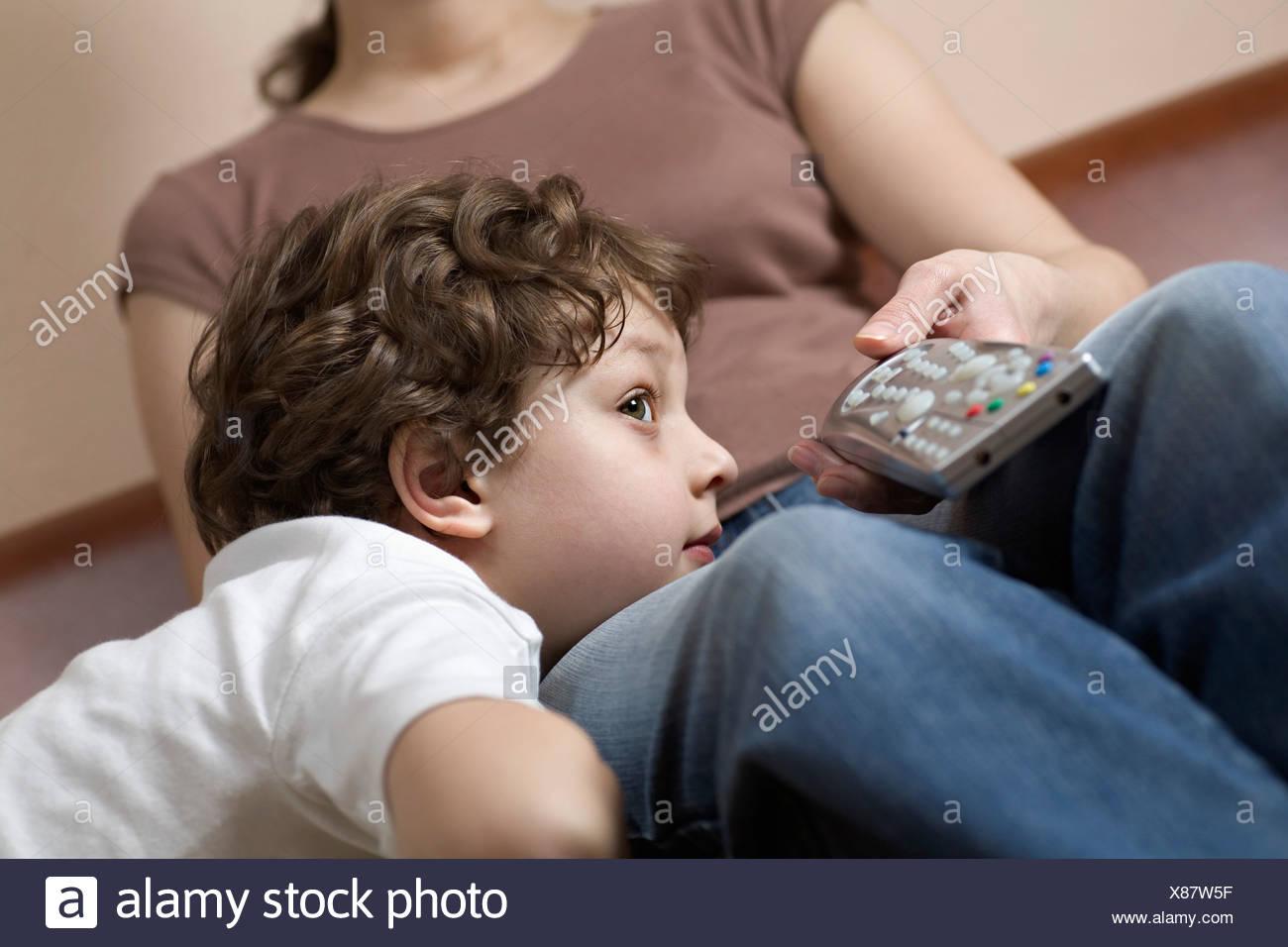 Un jeune garçon se reposant sa tête sur la jambe de sa mère, regarder la télévision Photo Stock
