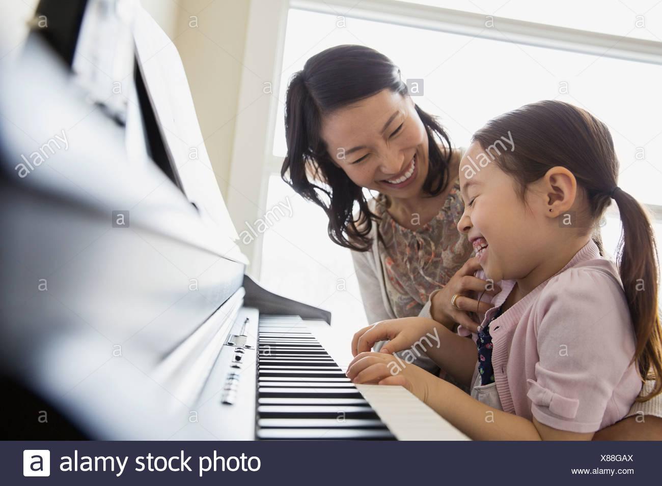 L'enseignement de mère fille à jouer du piano Photo Stock