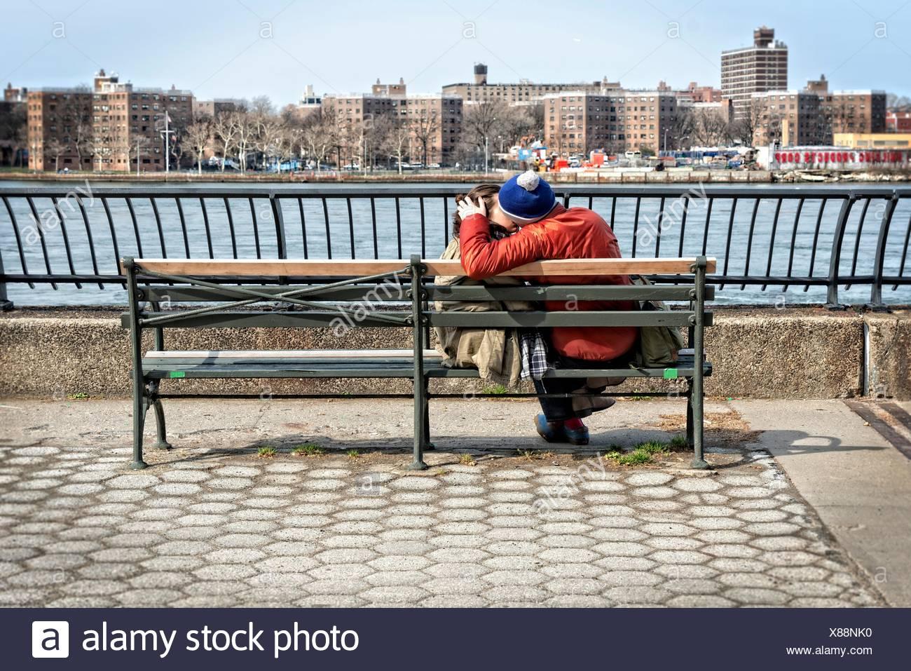Jeune homme et femme couple (entre 20 à 30 ans), avec amour, baiser sur un banc de la promenade. Photo Stock
