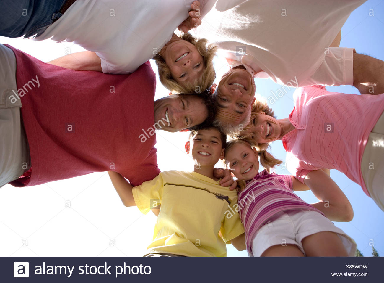 Three generation family smiling portrait huddle en vue vers le haut Photo Stock