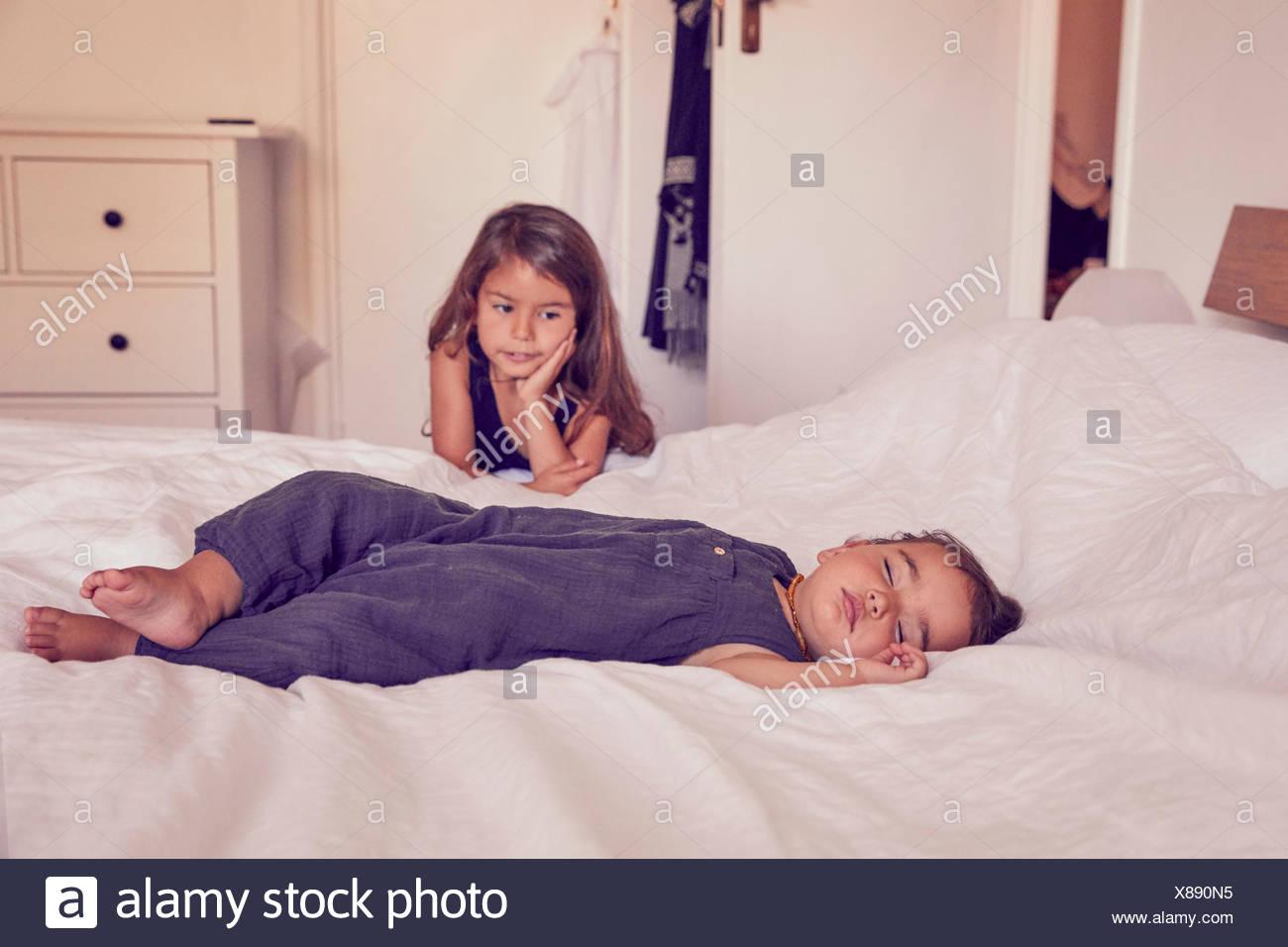 Female toddler, dormir sur un lit, grande sœur la regarder dormir Photo Stock