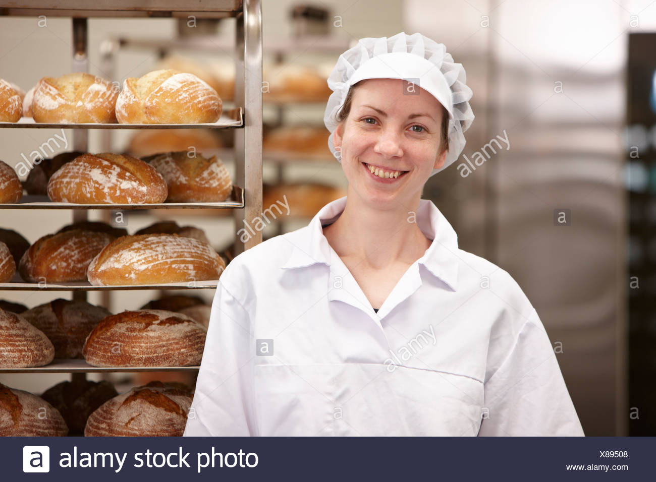 Smiling chef standing in kitchen Photo Stock
