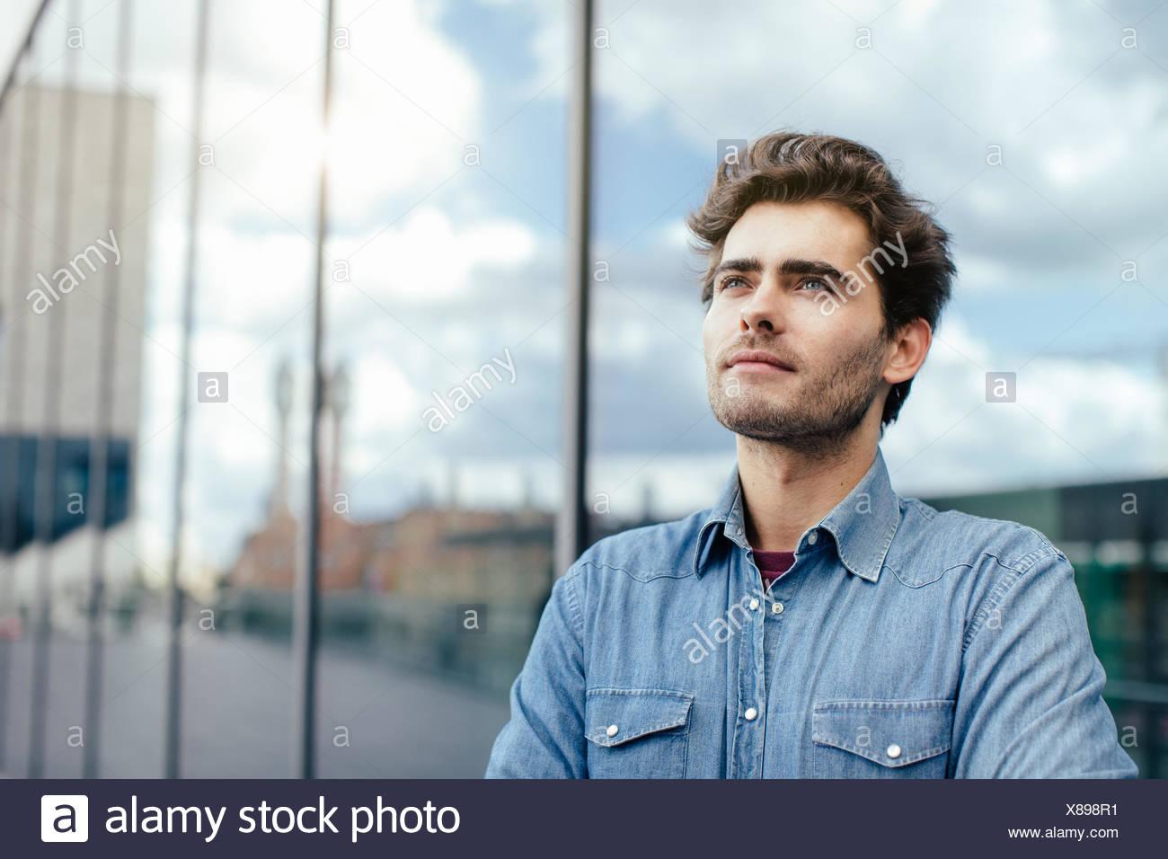 Jeune homme par fenêtre Photo Stock