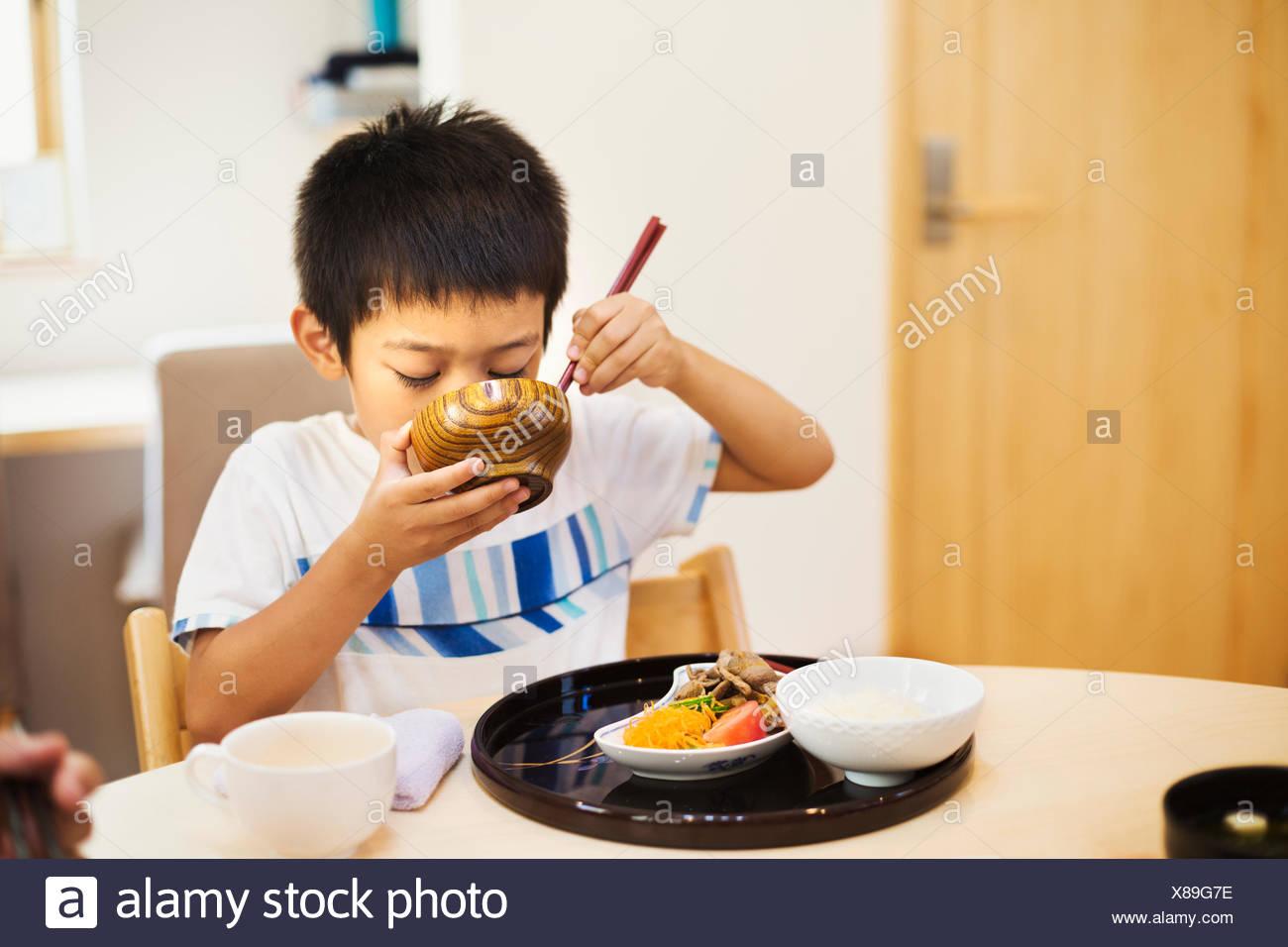 Maison de famille. Un garçon pour prendre un repas. Photo Stock