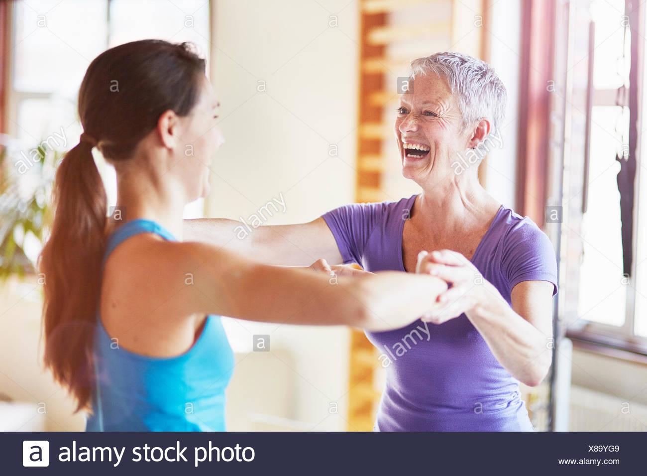 Jeune étudiante en riant avec l'enseignant en salle de sport pilates Photo Stock