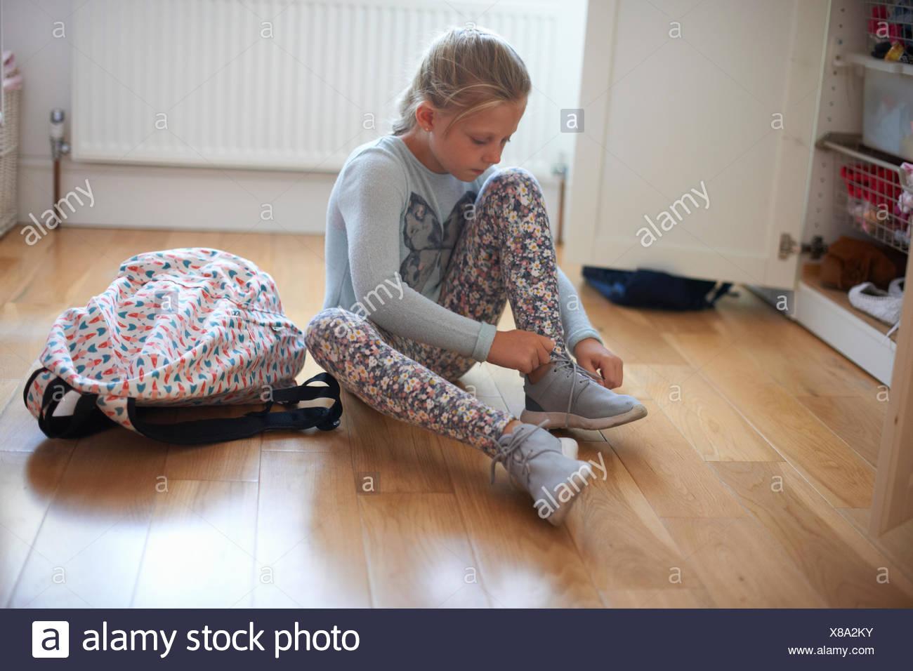 Fille assise sur le plancher de chambre à coucher attacher les lacets de butin Photo Stock