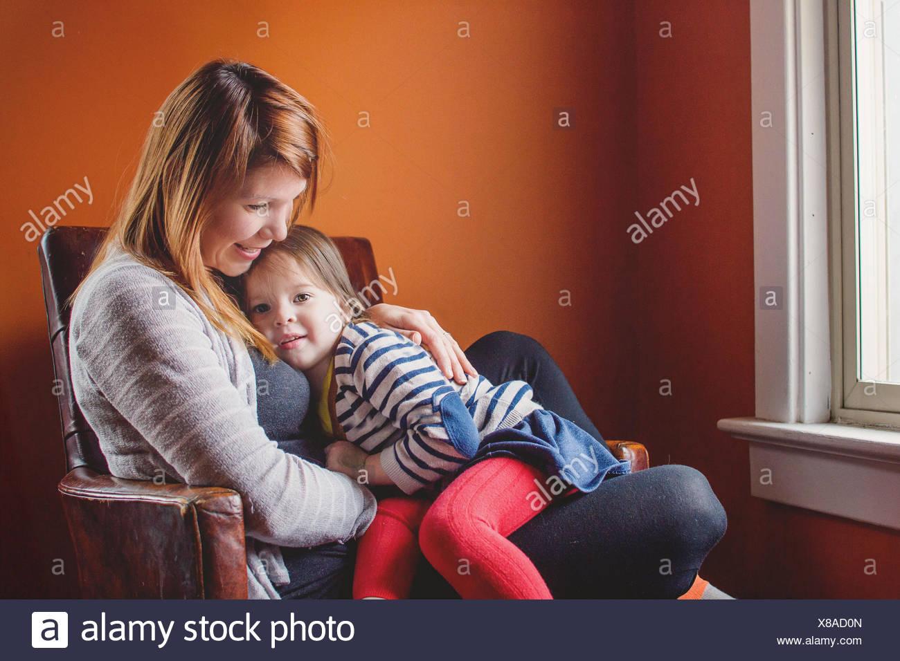 Mère et fille assise sur une chaise ensemble Photo Stock