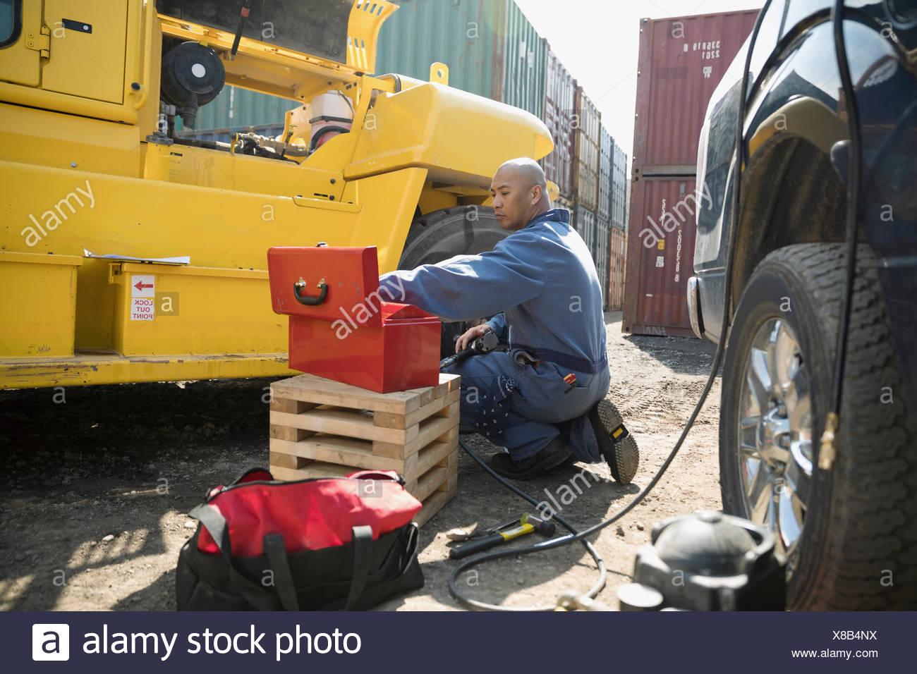 Mécanicien mâle avec fixation de la boîte à outils de la machinerie lourde en parc à conteneurs industriels Photo Stock