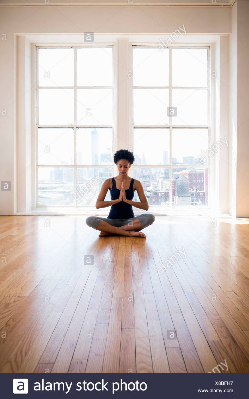 Woman practicing yoga in room Photo Stock