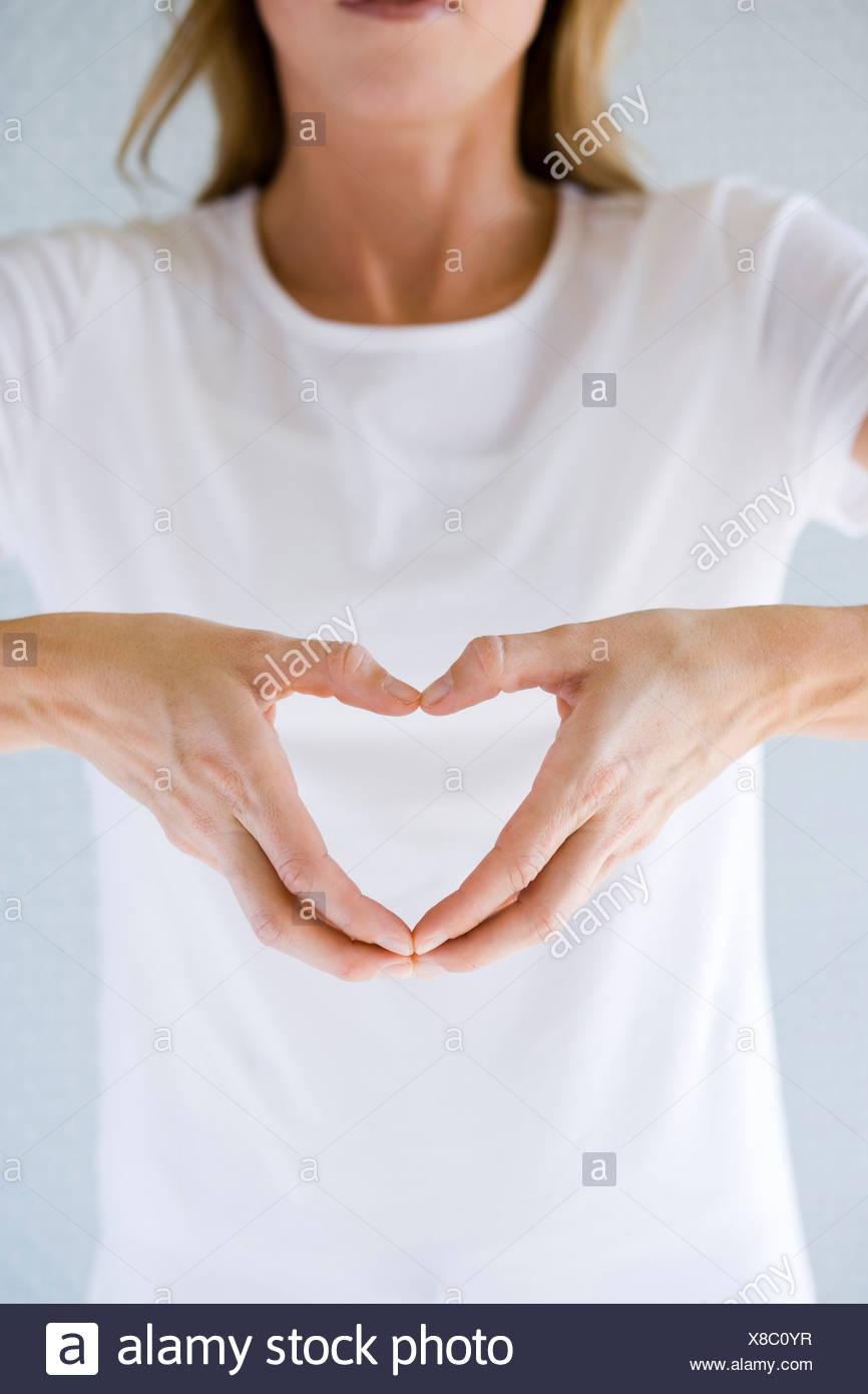 Femme faisant un cœur avec ses mains. Photo Stock