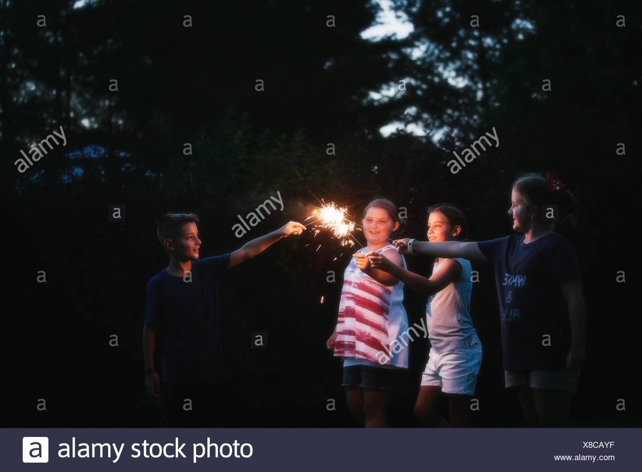 Garçon et trois filles d'allumer des cierges merveilleux ensemble de nuit le jour de l'indépendance, USA Photo Stock