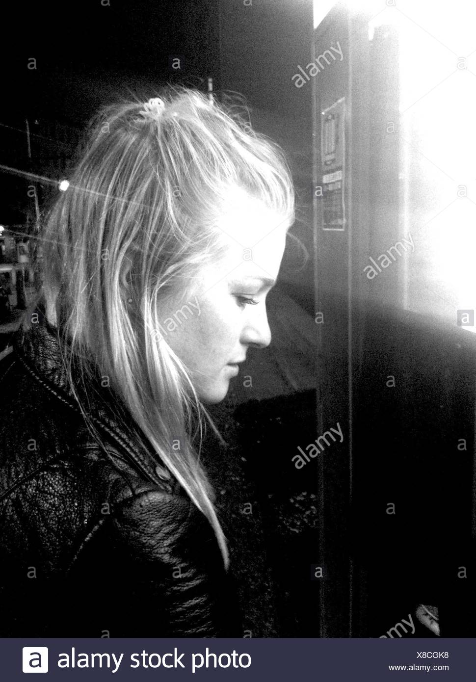 Vue de profil de femme debout par Ticket Machine la nuit Photo Stock