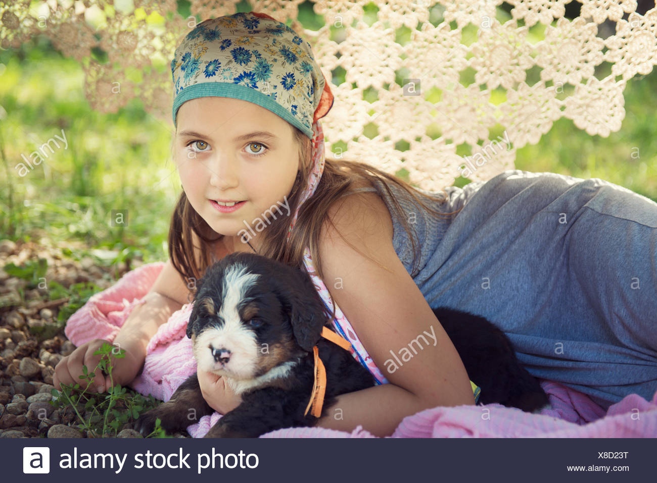 Girl allongé sous une table avec un chiot Photo Stock