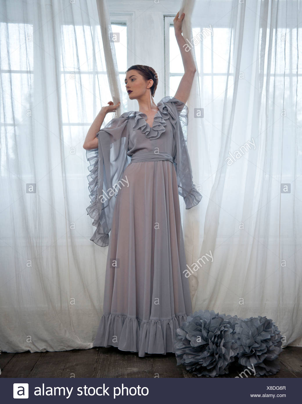 Une femme portant une longue robe grise, debout devant une fenêtre Banque D'Images