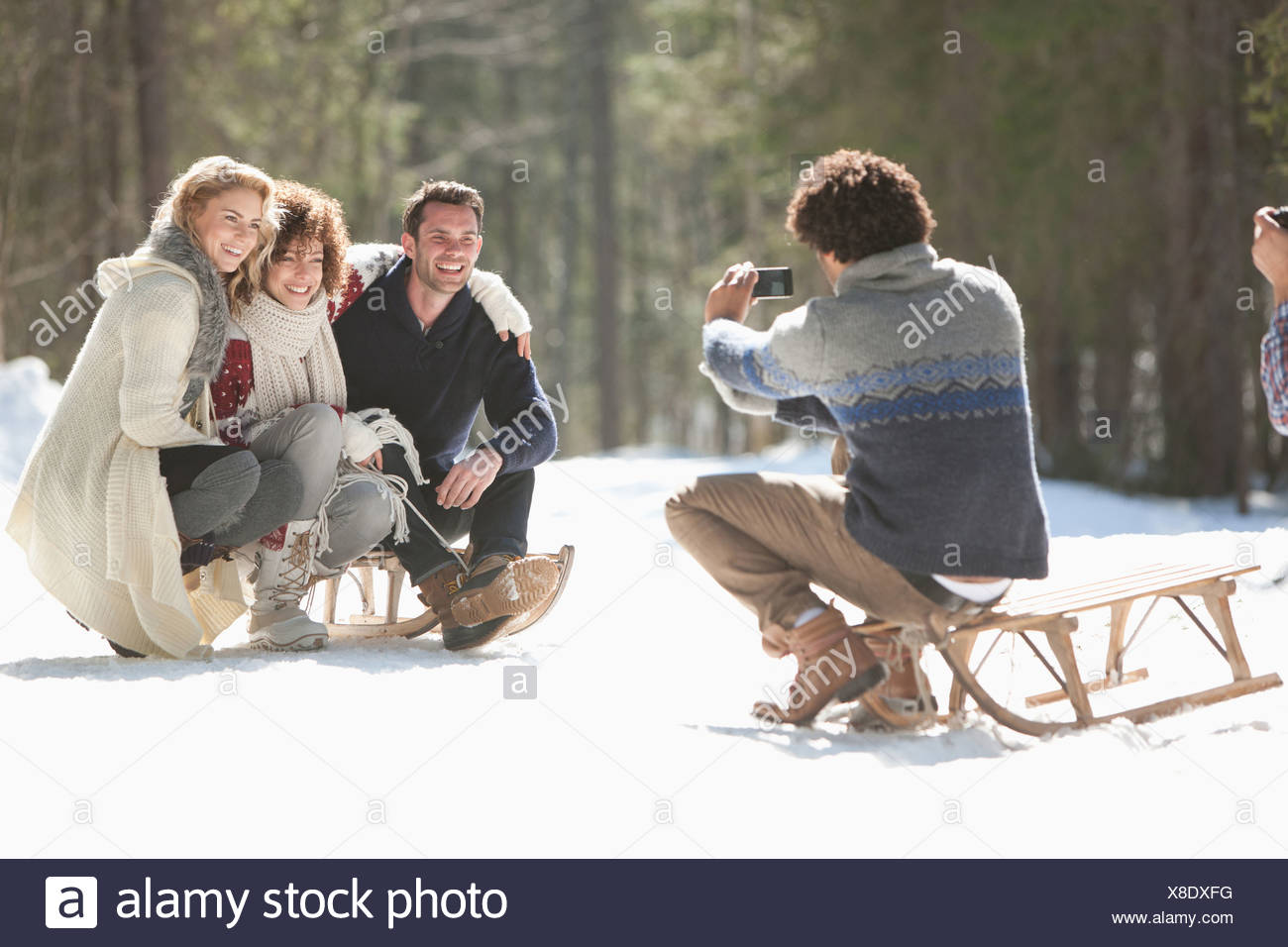 Quatre amis taking photograph in snowy landscape Photo Stock