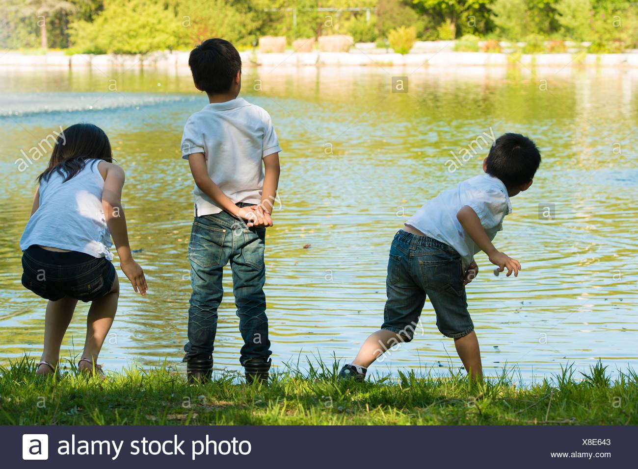 Trois enfants jouant près du lac Photo Stock