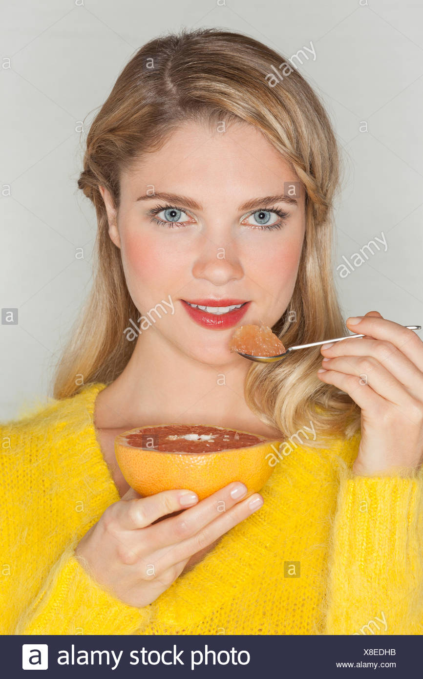 Portrait d'une femme belle de manger du pamplemousse Photo Stock