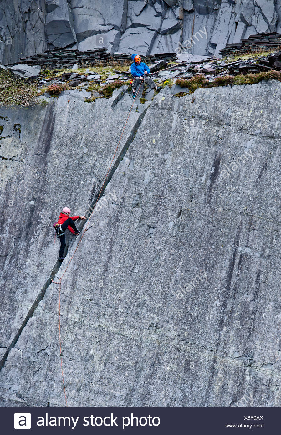 Les grimpeurs scaling steep rock face Photo Stock
