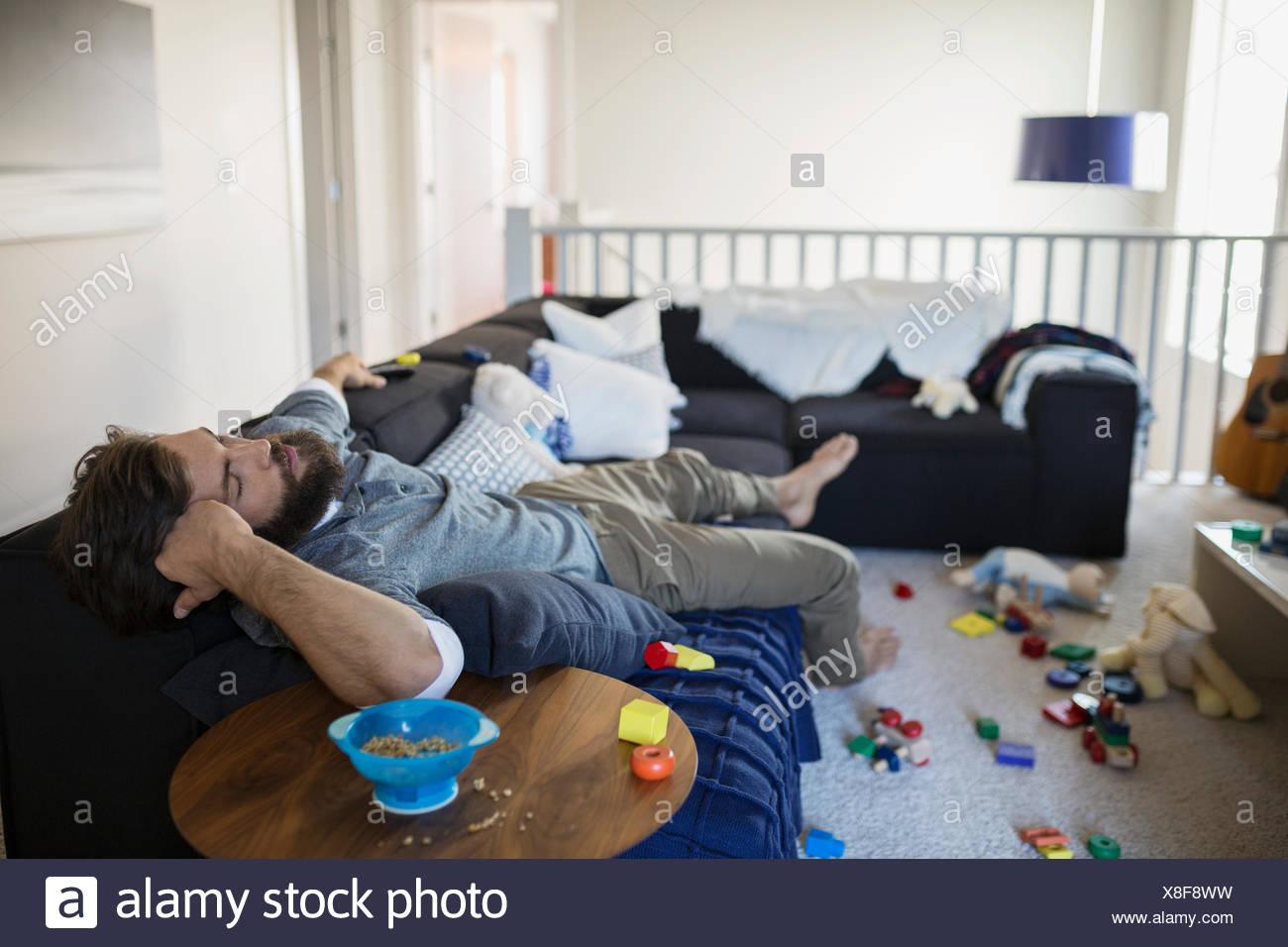 L'homme épuisé sieste sur canapé entouré par des jouets Photo Stock