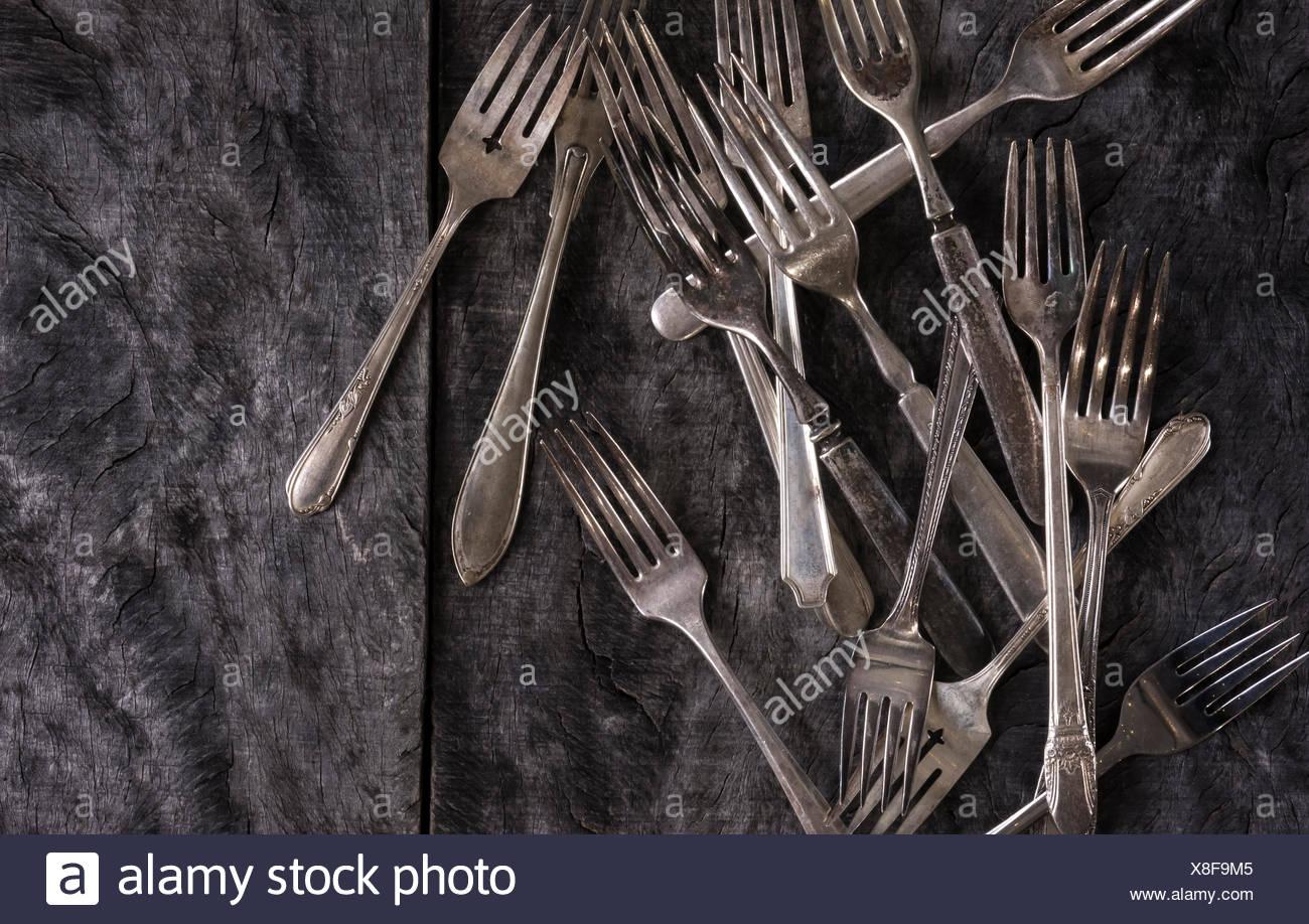Une gamme de fourches antiques dispersés sur une surface en bois gris rustique. Photo Stock