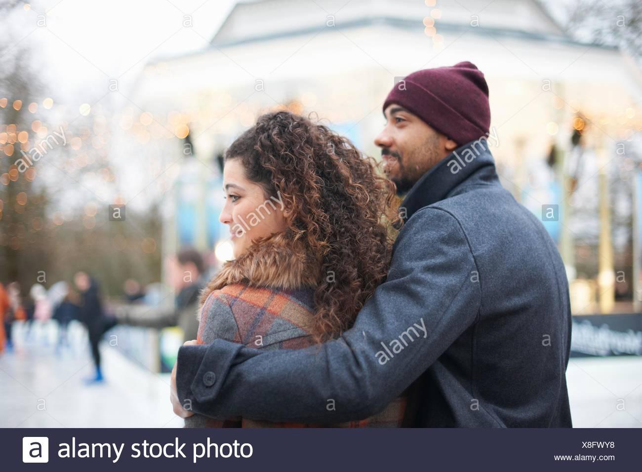 Vue arrière Mid adult man wearing Knit hat avec bras autour de young woman  smiling 6353bac0259b