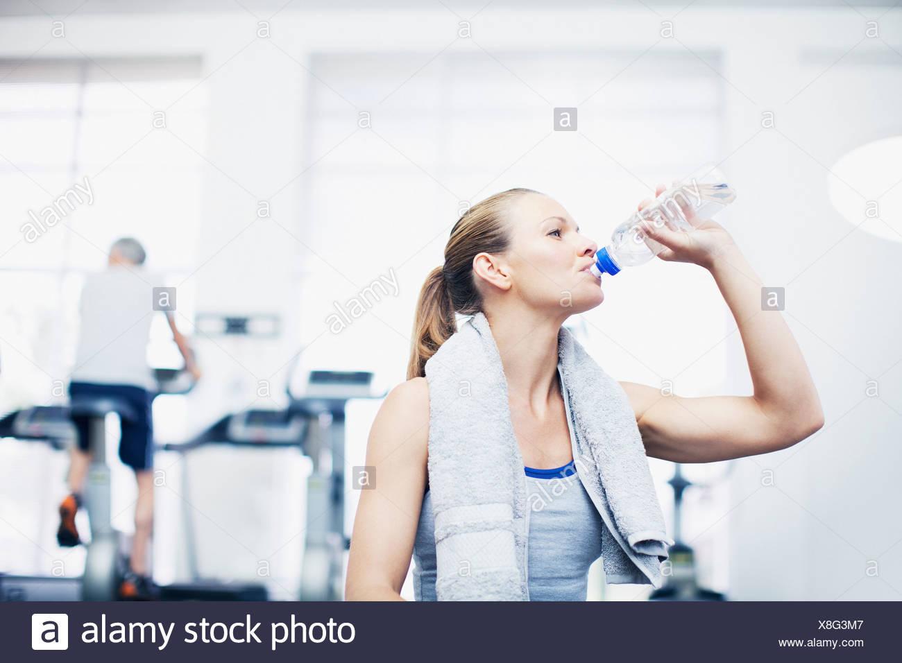 Femme avec une serviette autour du cou de l'eau potable dans un gymnase Photo Stock