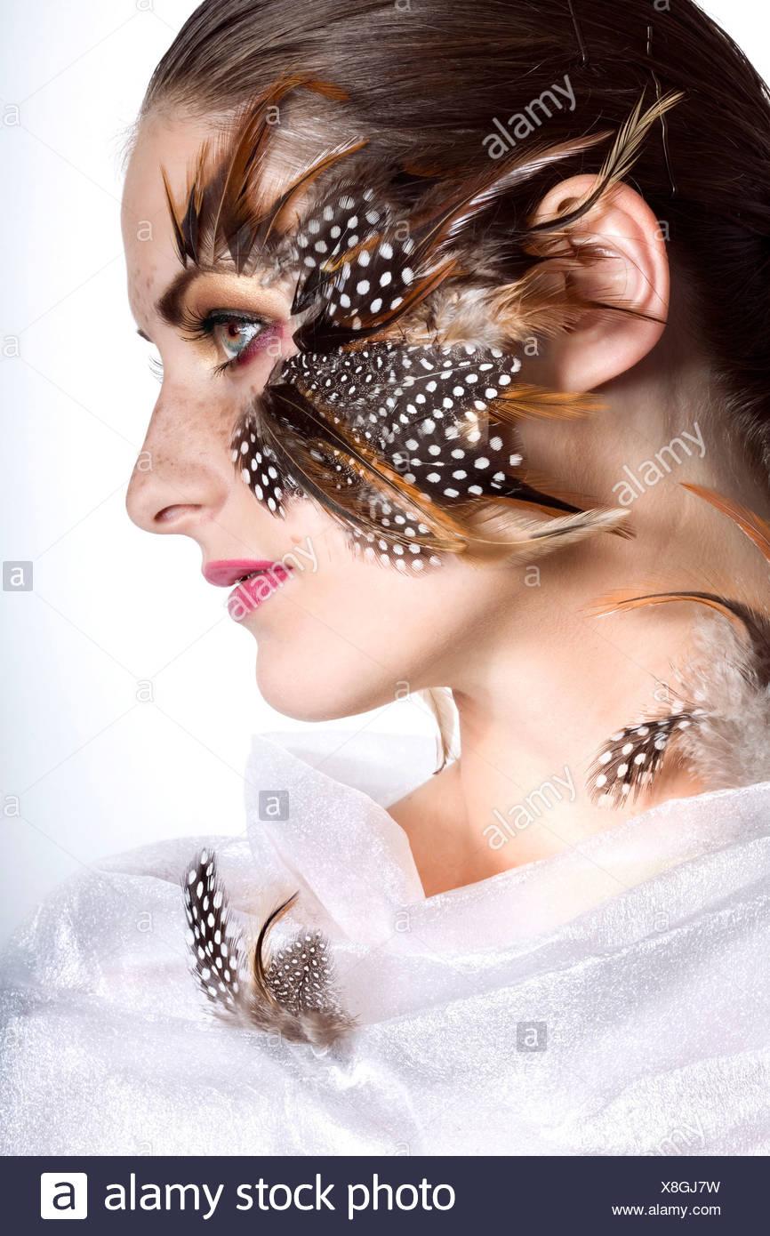 Jeune femme avec des plumes autour des yeux Photo Stock