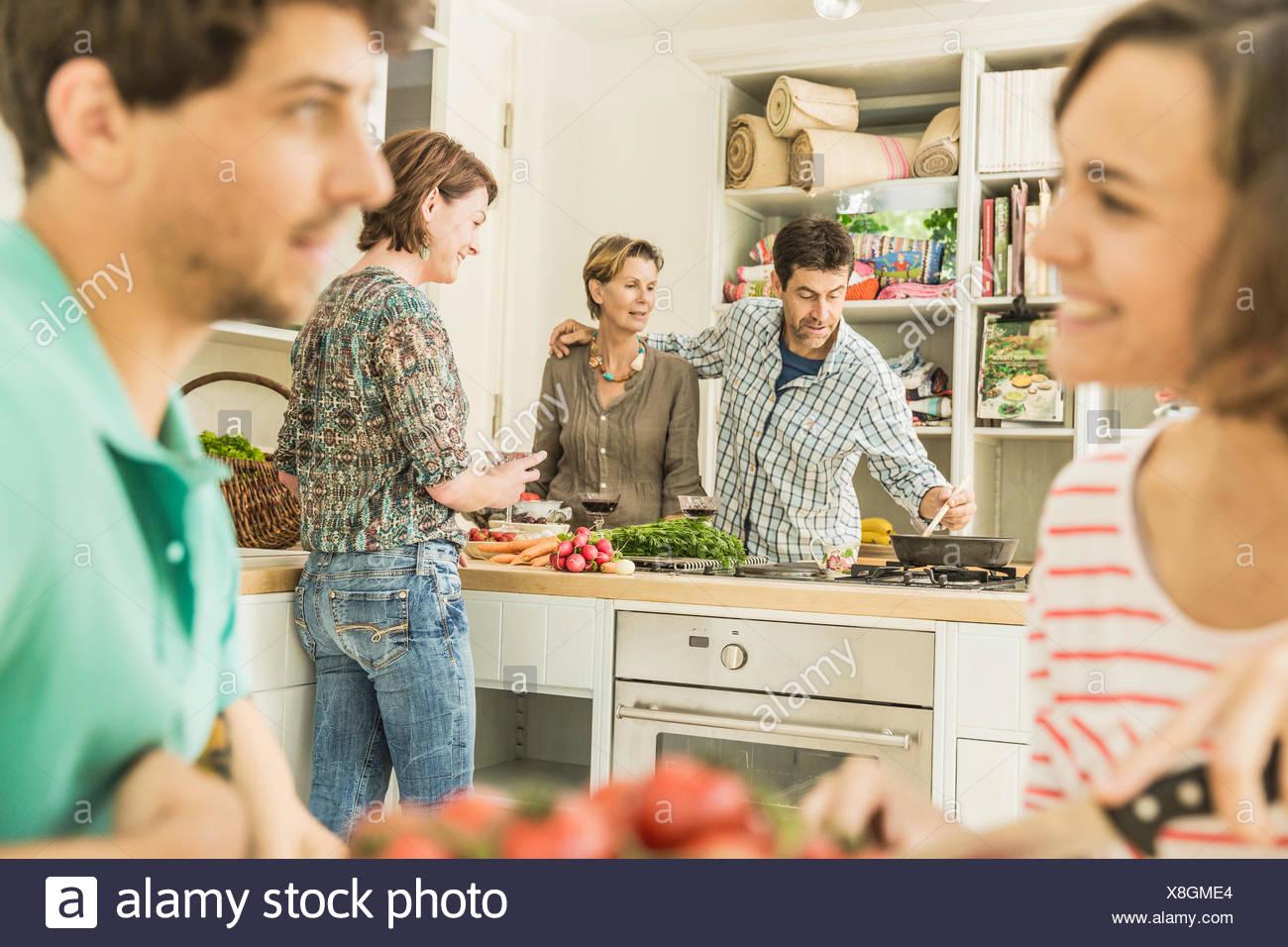 Cinq amis adultes rassemblement pour dîner dans la cuisine Photo Stock