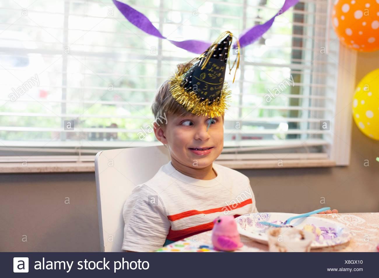 Boy in party hat assis à table en train de manger le gâteau d'anniversaire drôle de visage tirant Banque D'Images
