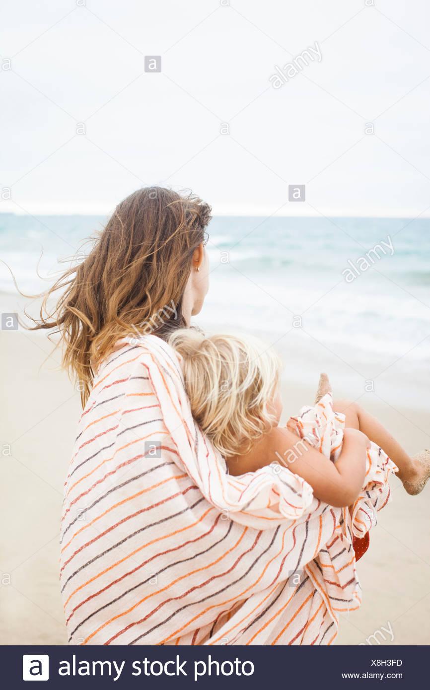 Vue arrière de la mère et l'enfant enveloppé dans une serviette à rayures Photo Stock