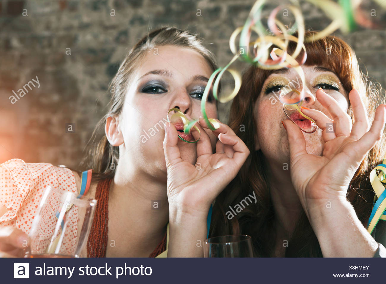 Allemagne, Berlin, Close up of young women blowing party streamers Photo Stock