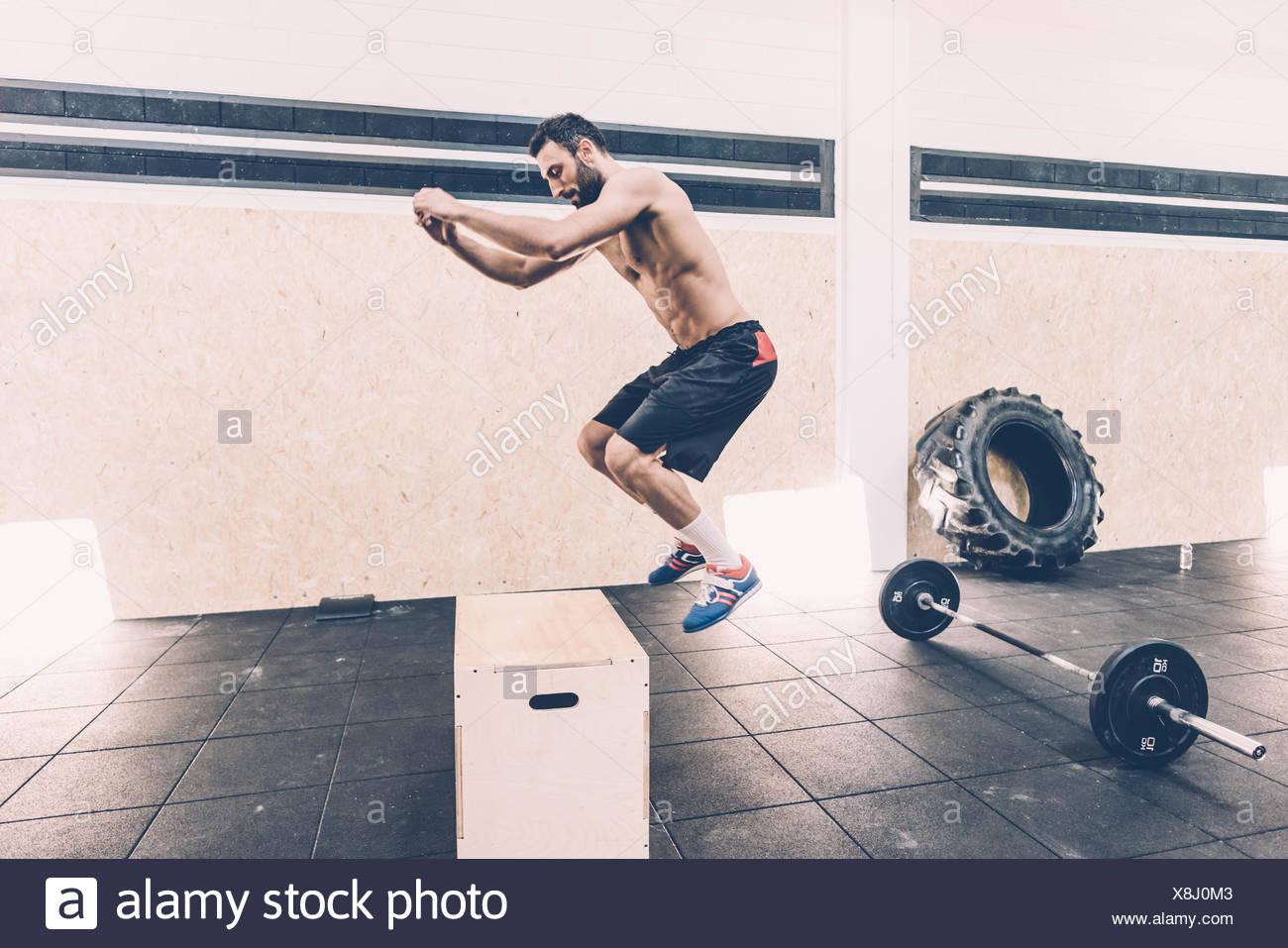 Jeune homme sautant sur fort à l'entraînement en salle de sport Photo Stock
