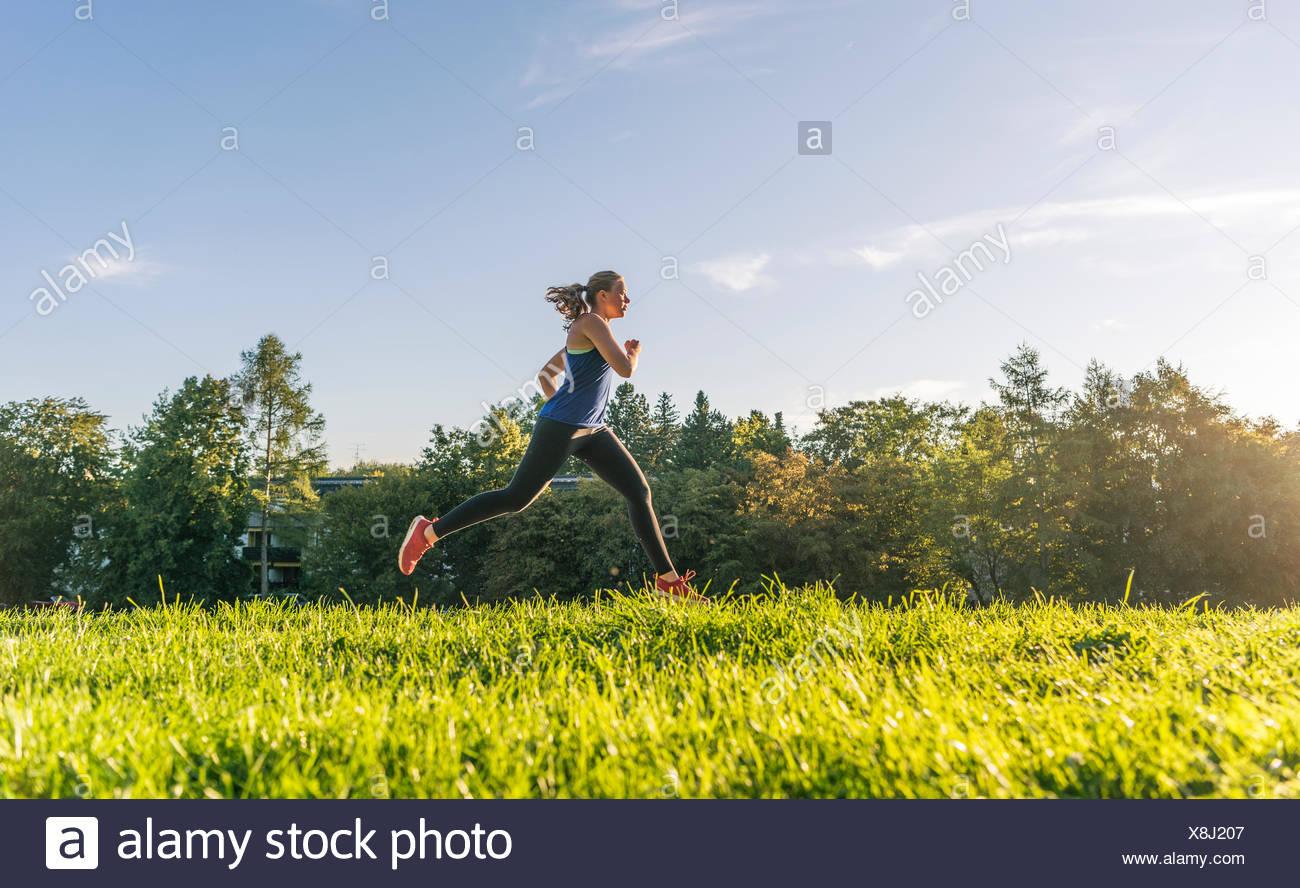 Jeune femme dans les vêtements de sport jogging en Park, Munich, Haute-Bavière, Bavière, Allemagne Photo Stock