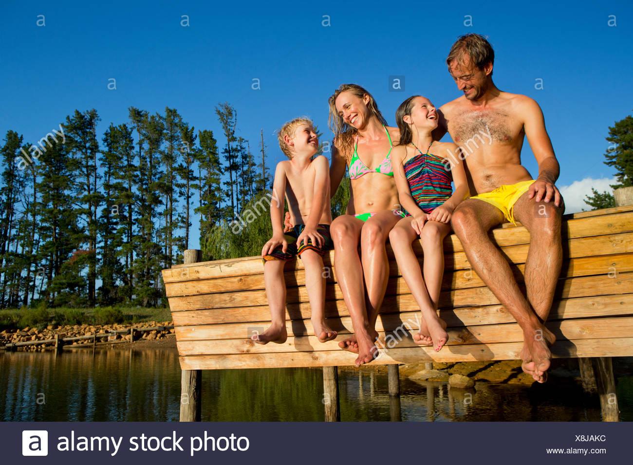 Portrait de famille heureuse assis sur jetée à côté lac Photo Stock