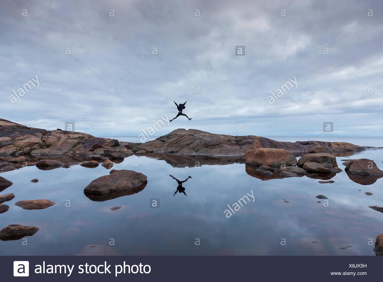 Femme sautant sur la roche par un lac en Suède, Allemagne Photo Stock