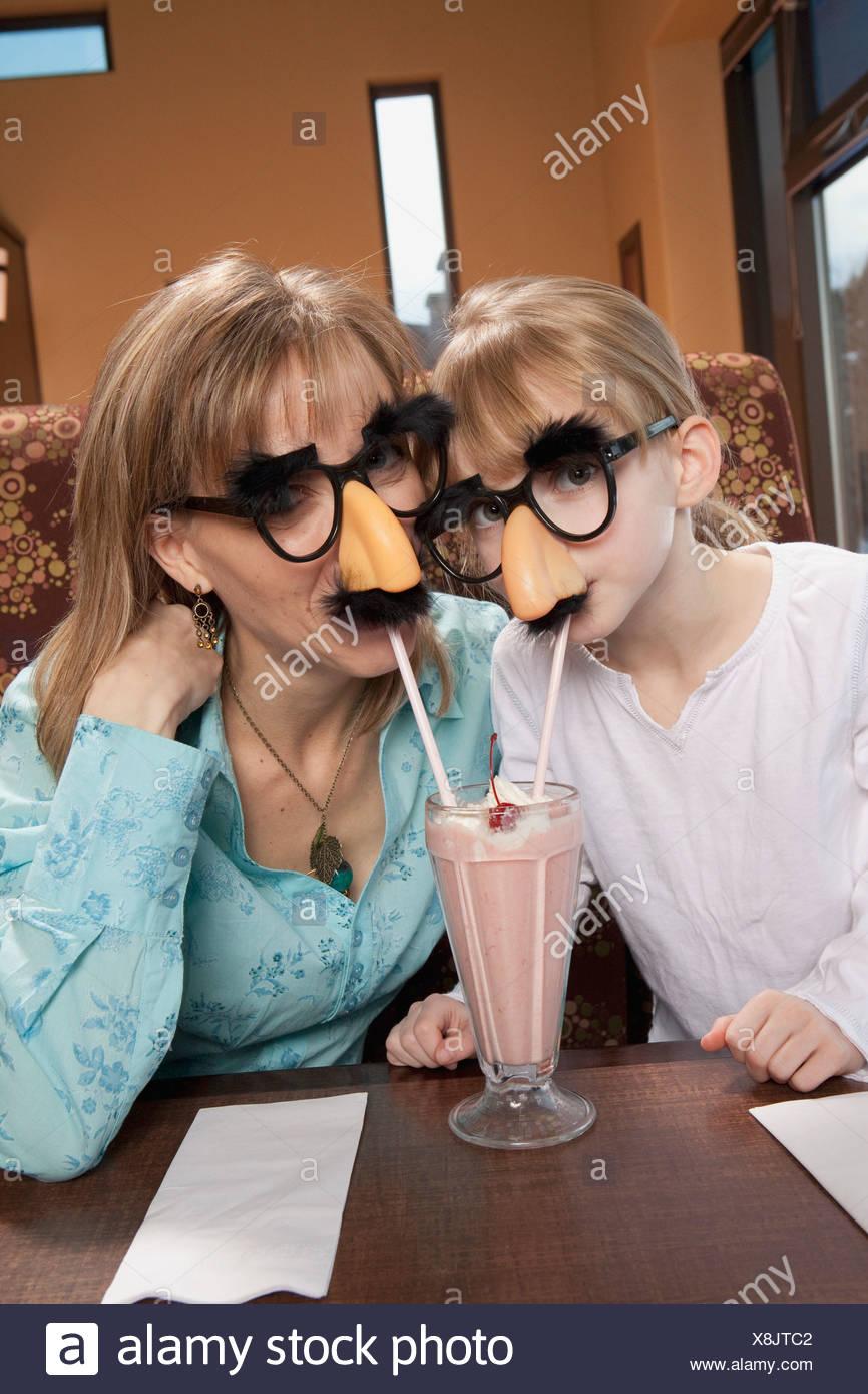 Mère et fille partager milkshake déguisé Photo Stock