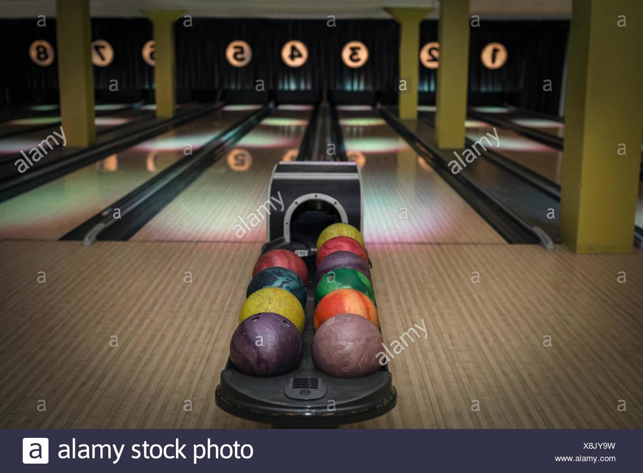 Boules multicolores sur rack au bowling Photo Stock