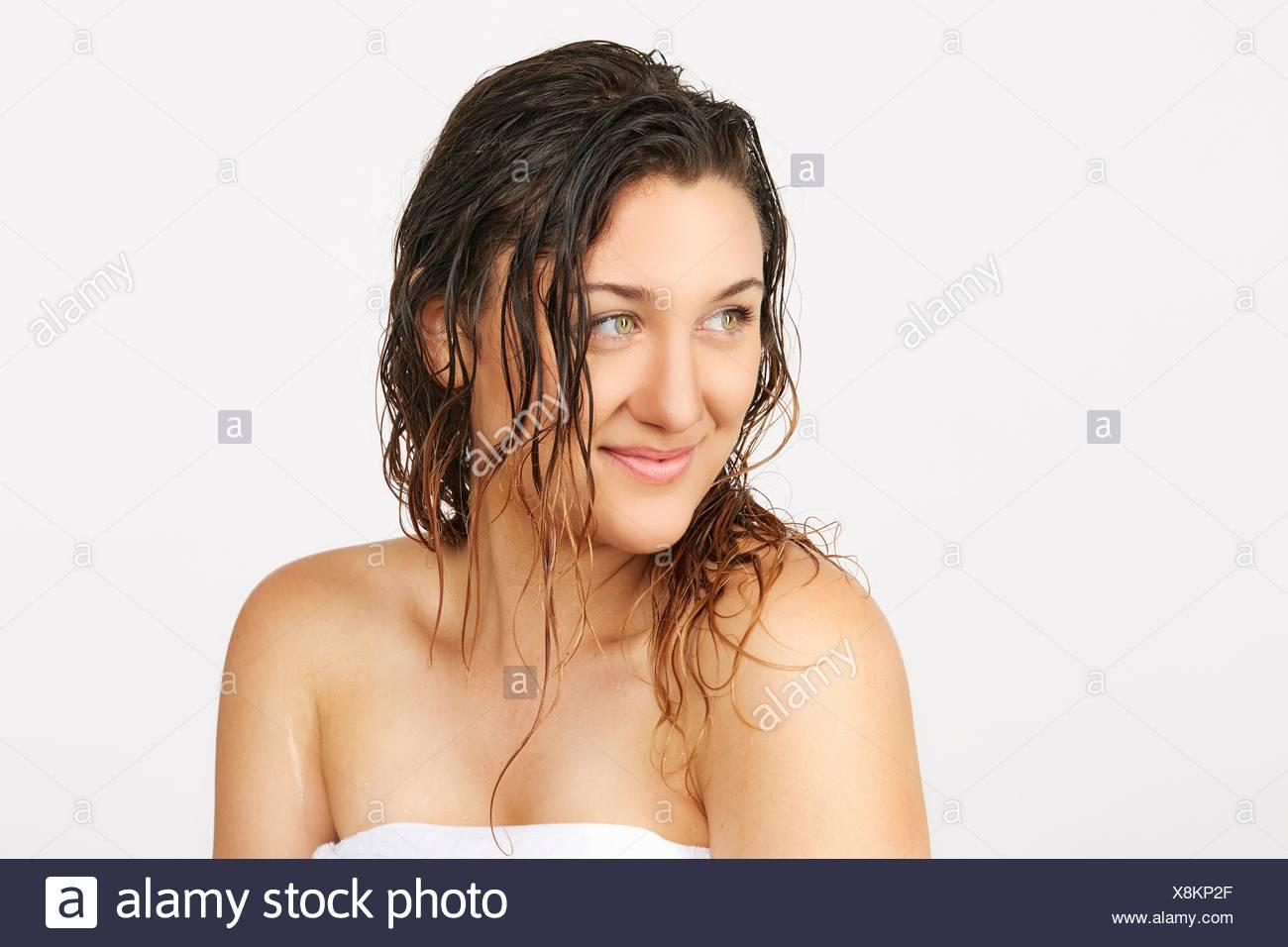 Jeune femme avec des cheveux humides portant serviette Photo Stock